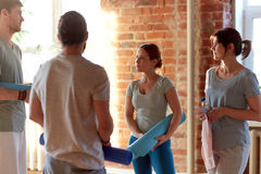 Groupe de personnes avec des tapis au studio ou au gymnase de yoga Images libres de droits