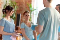 Groupe de personnes avec des tapis au studio ou au gymnase de yoga Images stock