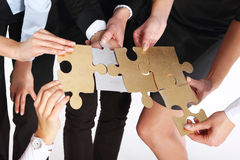 Groupe de personnes avec les puzzles argentés d'or Image libre de droits
