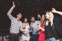Groupe de personnes ayant une partie sur le toit, ouvrant une bouteille de champagne Photographie stock libre de droits