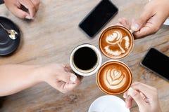 Groupe de personnes ayant une r?union apr?s n?gociation r?ussie d'affaires dans un caf? Caf? chaud potable d'art de latte de bois photos libres de droits