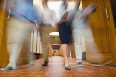 Groupe de personnes brouillées marchant par des portes ouvertes Image stock