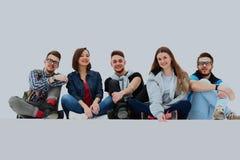 Groupe de personnes causal s'asseyant sur le plancher d'isolement photos stock