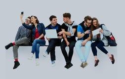 Groupe de personnes causal s'asseyant sur le plancher d'isolement photo stock