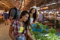 Groupe de personnes choisissant des herbes aromatiques sur les produits de sourire heureux d'achat d'amis de marché en plein air  Photographie stock