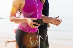Groupe de personnes coureurs sur le plan rapproché de plage de jeunes coureurs de sport pulsant ensemble l'élaboration au bord de Photographie stock libre de droits