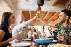 Groupe de personnes dînant et donnant la haute cinq Images stock