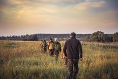 Groupe de personnes dans une rangée passant loin par le champ rural au coucher du soleil pendant la saison de chasse dans la camp photo libre de droits
