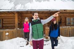 Groupe de personnes de doigt de point d'homme près de cottage en bois de station de vacances de neige d'hiver de maison de campag Image stock