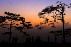 Groupe de personnes de silhouette se tenant dans le coucher du soleil Photographie stock