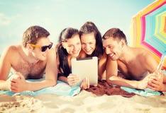 Groupe de personnes de sourire avec le PC de comprimé sur la plage Photographie stock