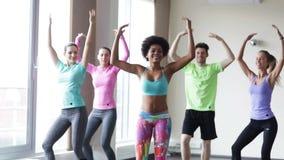 Groupe de personnes de sourire dansant dans le gymnase ou le studio banque de vidéos