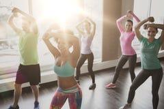 Groupe de personnes de sourire dansant dans le gymnase ou le studio Photo stock