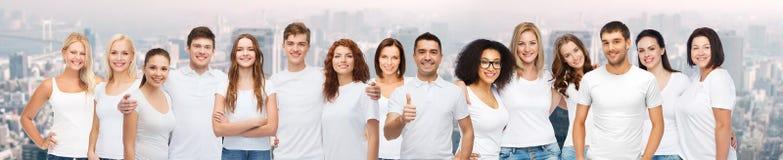 Groupe de personnes différentes heureuses dans des T-shirts blancs photographie stock libre de droits