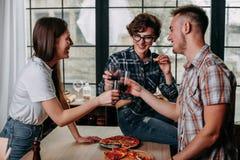 Groupe de personnes dinant ensemble Célébration et clinkin d'amis Image stock