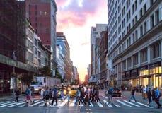 Groupe de personnes divers marchant à travers une intersection occupée à New York City image stock