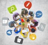 Groupe de personnes divers travaillant autour du Tableau Images stock
