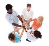 Groupe de personnes empilant des mains ensemble Images stock