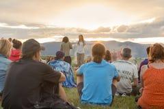 Groupe de personnes en nature appréciant le coucher du soleil Images libres de droits