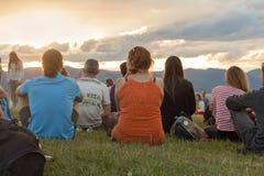 Groupe de personnes en nature appréciant le coucher du soleil Photographie stock
