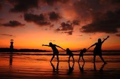 Groupe de personnes sur la plage dans le coucher du soleil Photo libre de droits