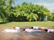 Groupe de personnes faisant le yoga dehors et le mensonge Photographie stock