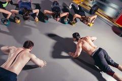 Groupe de personnes folâtres s'exerçant dans un gymnase Images stock