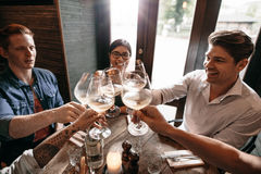 Groupe de personnes grillant le vin au restaurant Images stock