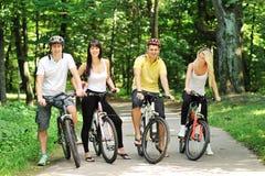 Groupe de personnes heureuses attirantes sur des bicyclettes dans la campagne Image libre de droits