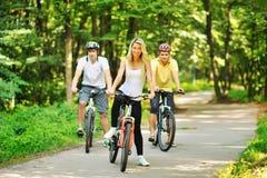 Groupe de personnes heureuses attirantes sur des bicyclettes dans la campagne Photo libre de droits