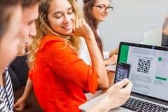 Groupe de personnes heureuses avec l'ordinateur portable en café Photo libre de droits