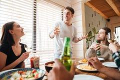 Groupe de personnes heureuses buvant et célébrant à la table Image libre de droits