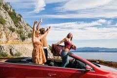 Groupe de personnes heureuses dans la voiture convertible rouge Photo libre de droits