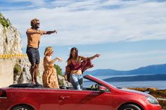 Groupe de personnes heureuses dans la voiture convertible rouge Photographie stock