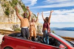 Groupe de personnes heureuses dans la voiture convertible rouge Image stock