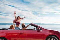 Groupe de personnes heureuses dans la voiture convertible rouge Photos stock