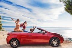Groupe de personnes heureuses dans la voiture convertible rouge Photo stock