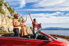 Groupe de personnes heureuses dans la voiture convertible rouge Images stock
