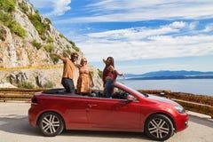 Groupe de personnes heureuses dans la voiture convertible rouge Photos libres de droits