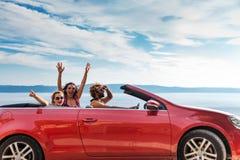 Groupe de personnes heureuses dans la voiture convertible rouge Image libre de droits