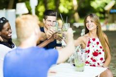 Groupe de personnes heureuses gaies grillant tout en se reposant à une table Images stock
