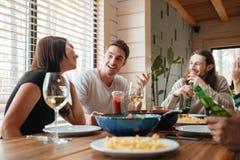 Groupe de personnes heureuses mangeant et parlant à la table Photos stock