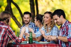 Groupe de personnes heureuses mangeant de la nourriture dehors photo libre de droits