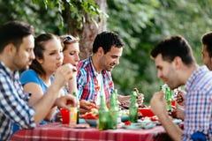 Groupe de personnes heureuses mangeant de la nourriture dehors image libre de droits
