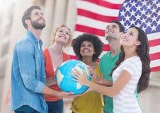 Groupe de personnes heureuses tenant le globe contre le drapeau américain et recherchant Images stock