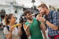 Groupe de personnes heureux mangeant de la pizza dehors Images stock