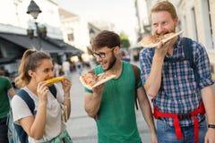 Groupe de personnes heureux mangeant de la pizza dehors Photos libres de droits