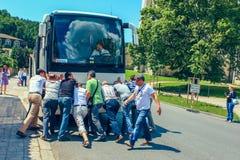 Groupe de personnes hommes poussant l'autobus cassé sur une route de campagne pour mettre en marche le moteur République Tchèque  photo stock