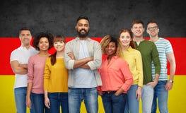 Groupe de personnes international au-dessus de drapeau allemand Photographie stock libre de droits