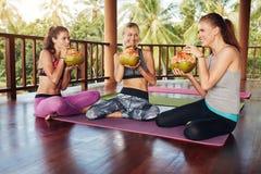 Groupe de personnes jus potable de noix de coco à la classe de yoga Photo stock